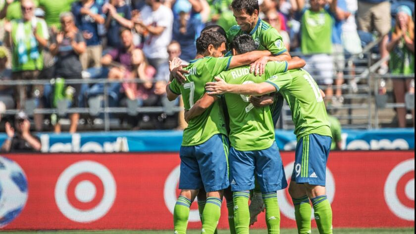 Seattle Sounders midfielder Nicolas Lodeiro, obscured, celebrates with his team after scoring against the LA Galaxy during a Major League Soccer match Saturday, Aug. 18, 2018, in Seattle.