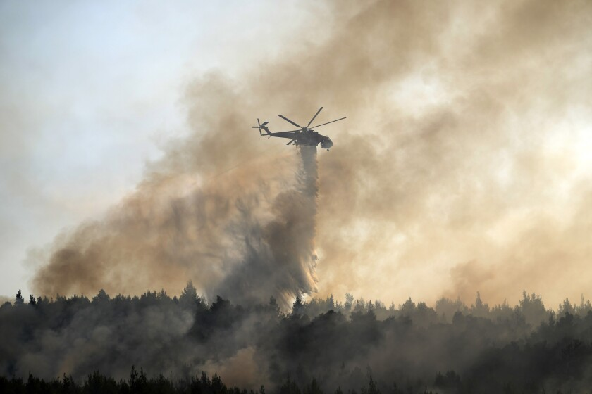 Helicopter dropping water over a fire in Greece