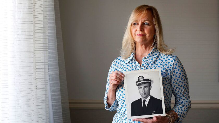 Deborah Crosby, 58, holds a photo of her father, Navy pilot Lt. Cmdr. Frederick Crosby. Deborah Cros