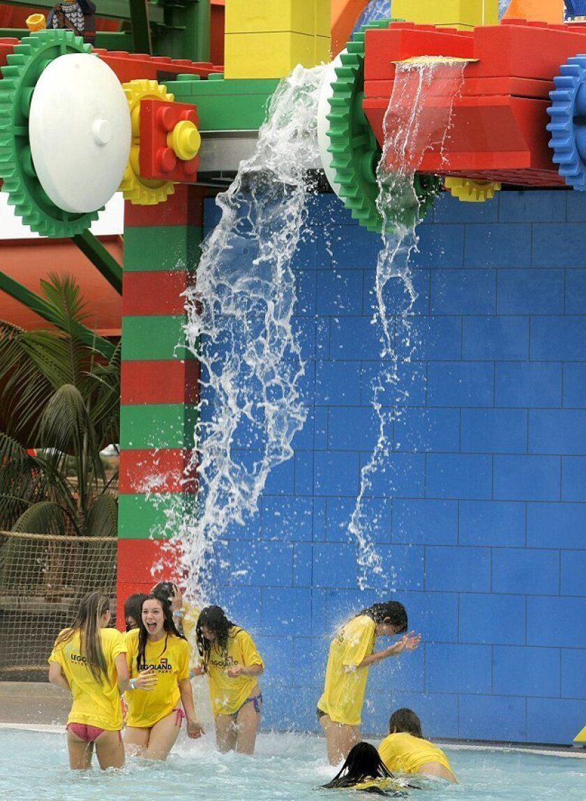 Teenagers play under a waterfall at Legoland's $12 million water park, which opened May 28.