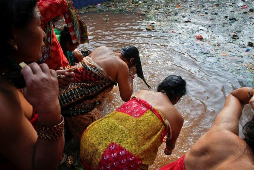 A Nepalese mother is dressed by her daughters after taking a holy bath at the sacred Matatirtha Shrine pond, on the outskirts of Kathmandu, Nepal, 06 May 2016. On 'Mother's Day', sons and daughters show their gratitude to their mothers in Nepal, bringing them presents. But those who have no mother anymore traditionally visit the Matatirtha Shrine for a commemoration. EPA/NARENDRA SHRESTHA