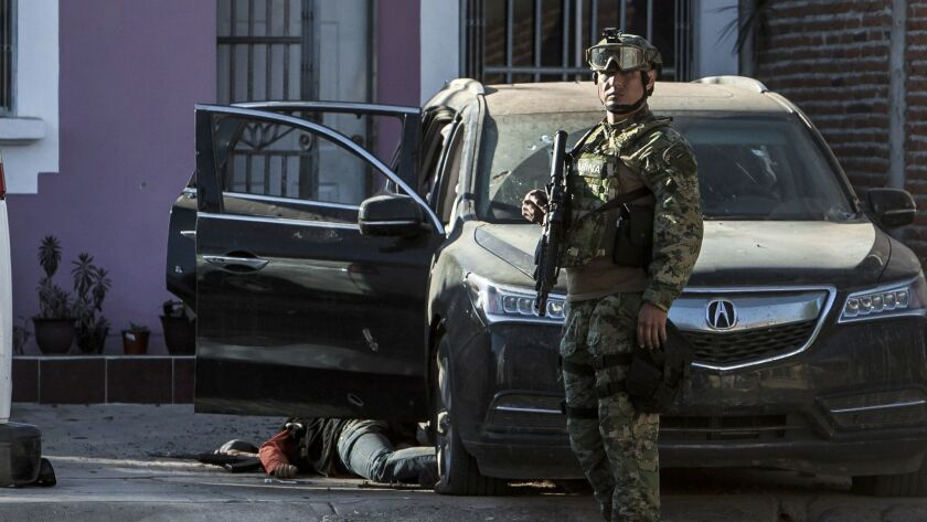 A Mexican marine stands by the body of a gunman after shots were exchanged in the city of Culiacan on Feb. 7. The Sinaloa state prosecutor's office said heavily armed men attacked the marines, leaving one of them dead.