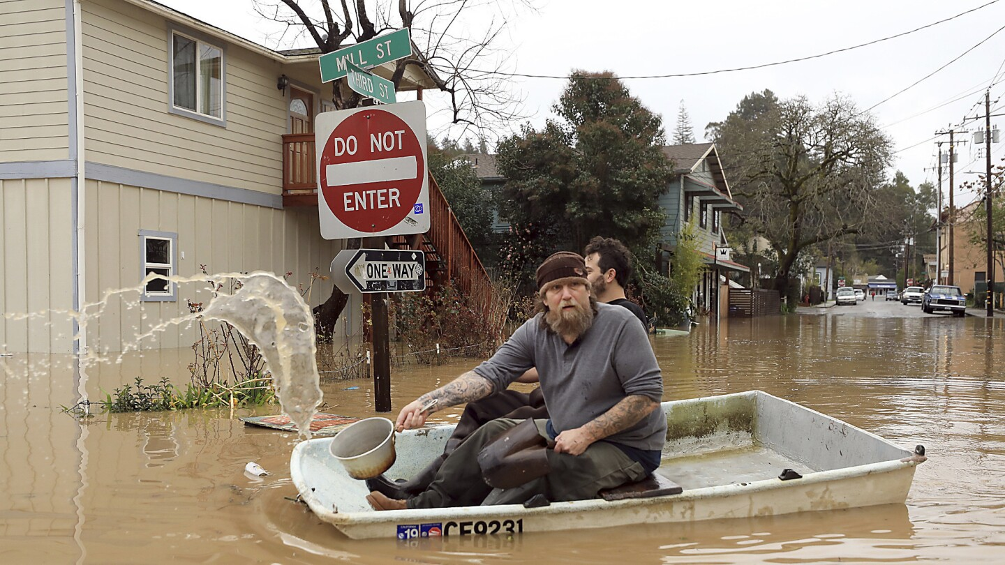 Jonathan Von Renner Jr. and a friend row past flooded Mill and Third streets in Guerneville, Calif., on Wednesday.