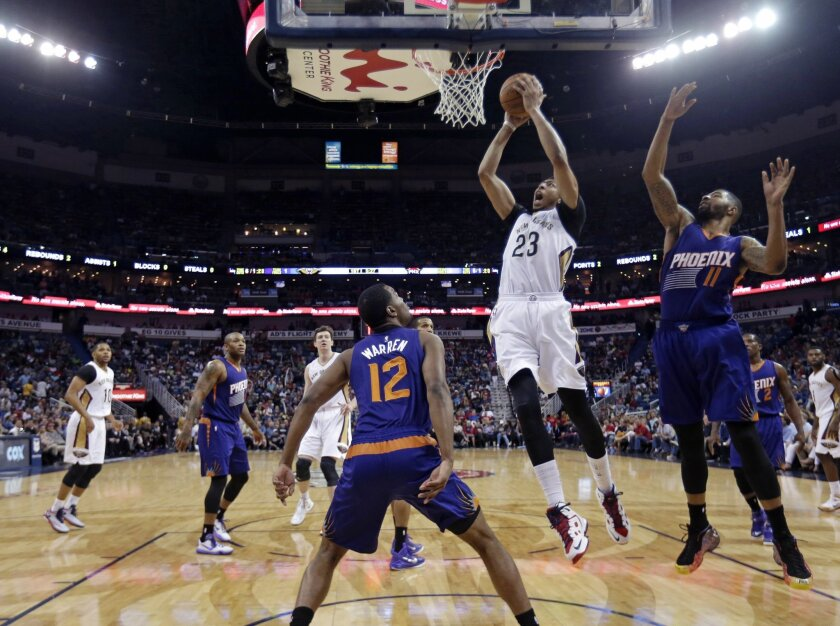 New Orleans Pelicans forward Anthony Davis (23) goes to the basket between Phoenix Suns forward Markieff Morris (11) and forward T.J. Warren (12) in the first half of an NBA basketball game in New Orleans, Friday, April 10, 2015. The Pelicans won 90-75. (AP Photo/Gerald Herbert)