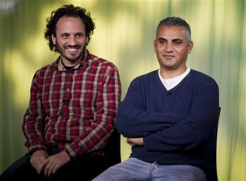 """In this Tues., Feb. 5, 2013 photo, documentary film Co-directors, Israeli, Guy Davidi, left, and Palestinian, Emad Burnat, pose for a photo after an interview in Los Angeles. Their 2011 documentary film, """"5 Broken Cameras,"""" is nominated for an Oscar in the best Documentary Feature category.  (AP Ph"""