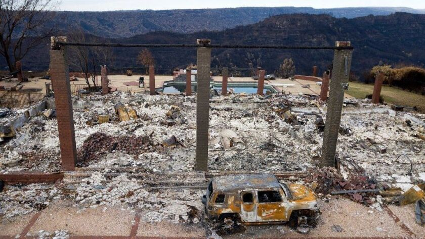 A burned vehicle sits in front of a home leveled by the Camp fire in Paradise, Calif.