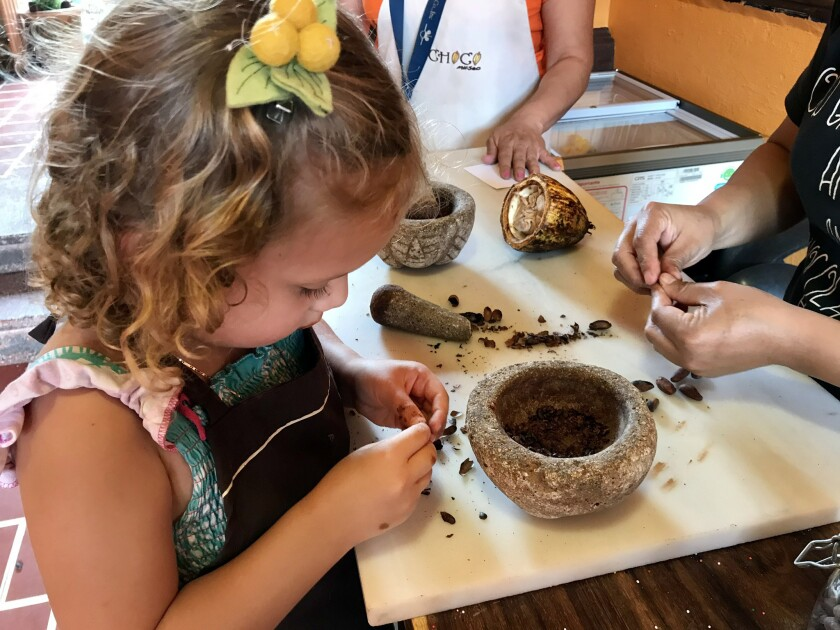 The reporter's daughter, Cora, separates the hulls from the interior nibs of roasted cocoa beans, be