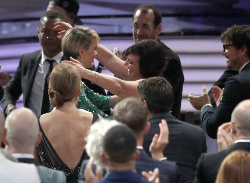 Sarah Paulson, center, hugs Marcia Clark after winning the Emmy for lead actress in a limited series or movie at the Emmy Awards at the Microsoft Theater in Los Angeles.