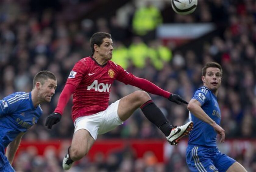 Manchester United's Javier Hernandez, centre, keeps the ball from Chelsea's Gary Cahill, left, and Cesar Azpilicueta during their English FA Cup quarterfinal soccer match at Old Trafford Stadium, Manchester, England, Sunday March 10, 2013. (AP Photo/Jon Super)