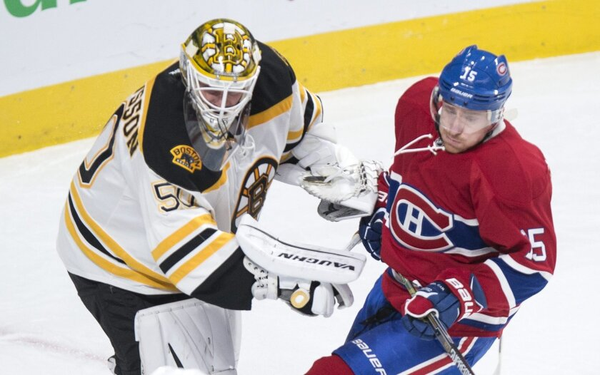 Boston Bruins' goalie Jonas Gustavsson, left, fends off Montreal Canadiens' Tomas Fleischmann during first period NHL hockey action, in Montreal, on Saturday, Nov. 7, 2015. (Paul Chiasson/The Canadian Press via AP)