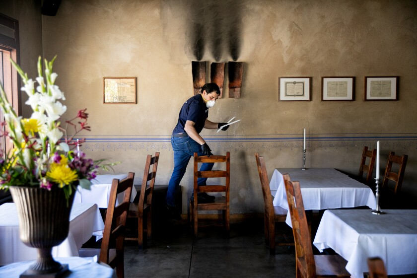 Server Leoonel Serrentino lights candles at Bleu Boheme restaurant in San Diego as it prepared to reopen in May