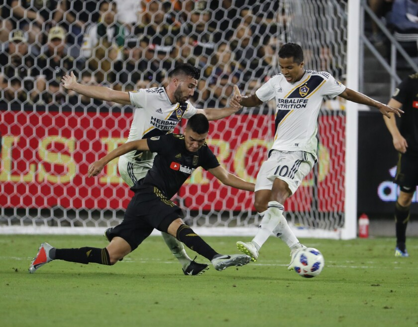 Galaxy midfielder Romain Alessandrini, left, and forward Giovani dos Santos, right, battle LAFC midfielder Eduard Atuesta, center, for control of the ball in the second half against the LAFC at the Banc of California Stadium.