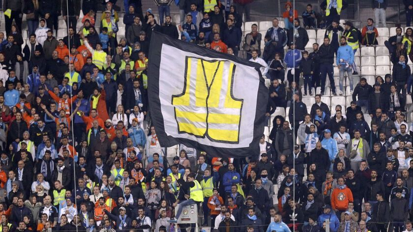 A supporter of Marseille waves a flag representing a giant yellow jacket, in solidarity with the mov