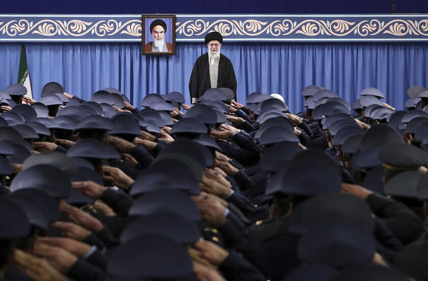 In this photo released by the official website of the Office of the Iranian Supreme Leader, Supreme Leader Ayatollah Ali Khamenei stands as army's air force and air defense staff salute at the start of their meeting in Tehran, Iran, Saturday, Feb. 8, 2020. A portrait of the late revolutionary founder Ayatollah Khomeini hangs in the background. (Office of the Iranian Supreme Leader via AP)