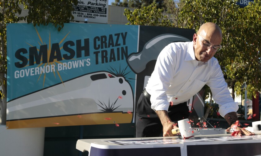 """Republican gubernatorial candidate Neel Kashkari smashes a plastic toy train at a Mobil gas station in Burbank, saying he was sending a message to Gov. Jerry Brown to """"stop the crazy train."""""""
