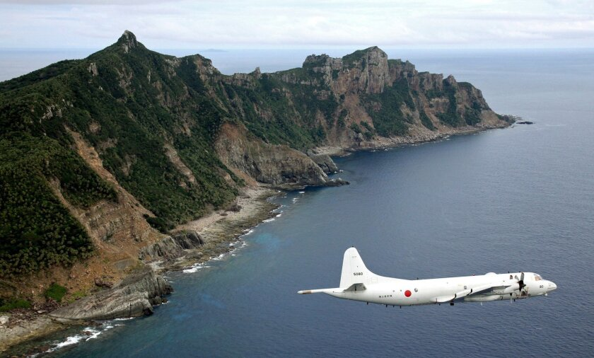 FILE - In this Oct. 13, 2011 file photo, Japan Maritime Self-Defense Force P-3C Orion surveillance plane flies over the disputed islands, called the Senkaku in Japan and Diaoyu in China, in the East China Sea. Japan says it will give names to five uninhabited islands as part of a group in the East