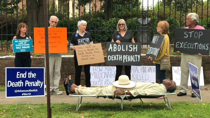 Arkansas Circuit Judge Wendell Griffen lies on a cot during a protest against the death penalty outside the governor's mansion in Little Rock, Ark., on Friday.