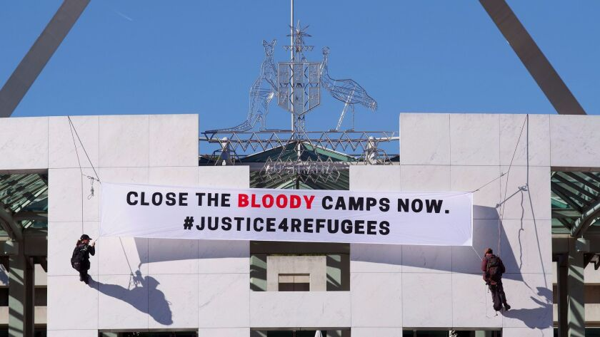 Protesters unfurl a banner at the Australian Parliament in Canberra on Dec. 1.