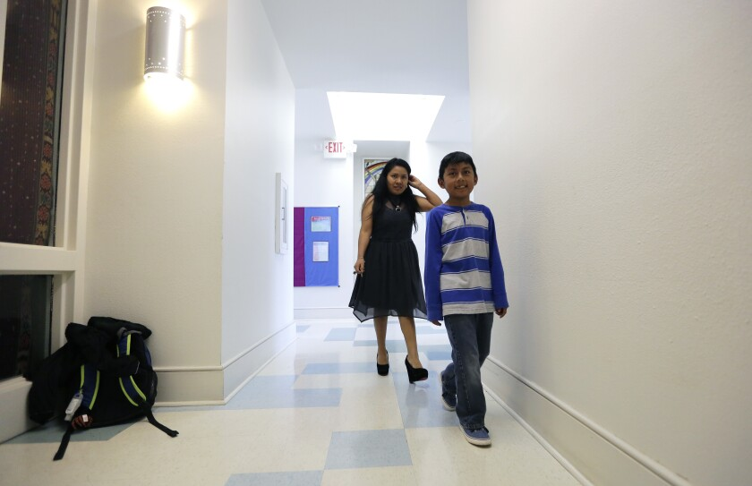 Hilda Ramirez and her son, Ivan, walk past the their living area at St. Andrew's Presbyterian Church.