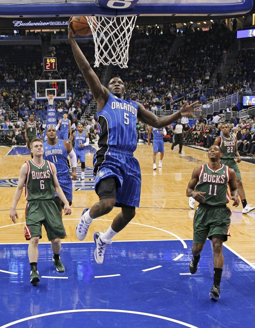 Orlando Magic's Victor Oladipo (5) makes a basket as he gets out in front of Milwaukee Bucks' Nate Wolters (6) and Brandon Knight (11) during the first half of an NBA basketball game in Orlando, Fla., Friday, Jan. 31, 2014. (AP Photo/John Raoux)