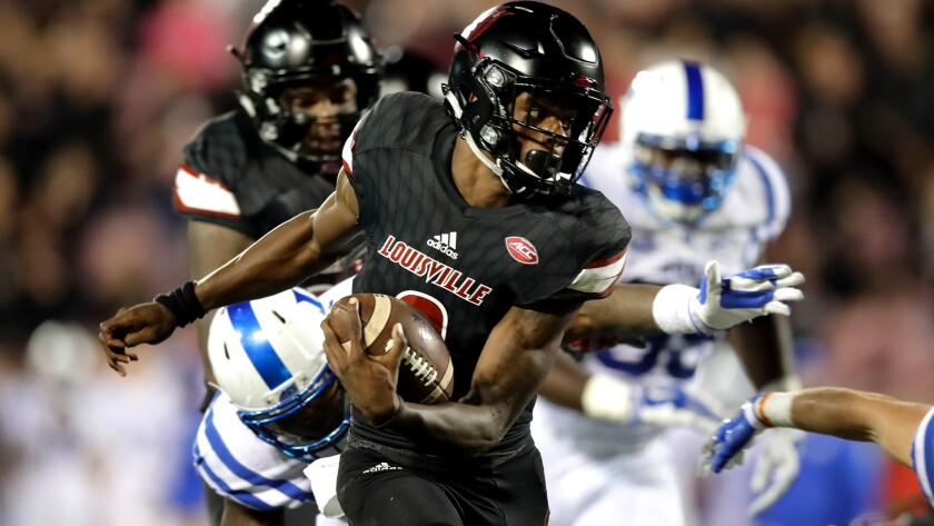 Louisville quarterback Lamar Jackson picks up yardage against Duke on Friday night.