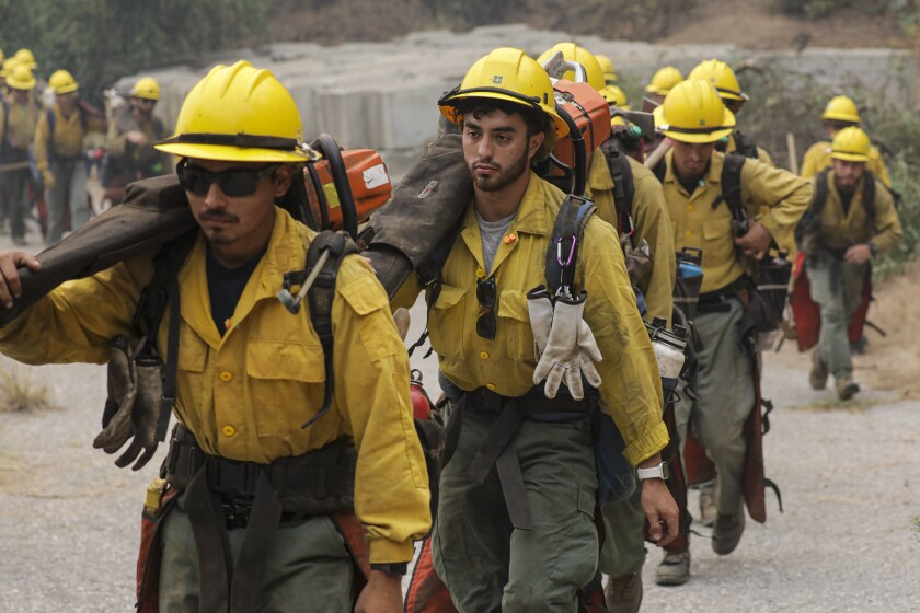 An Angeles National Forest fire crew heads into the forest to create a fire line.