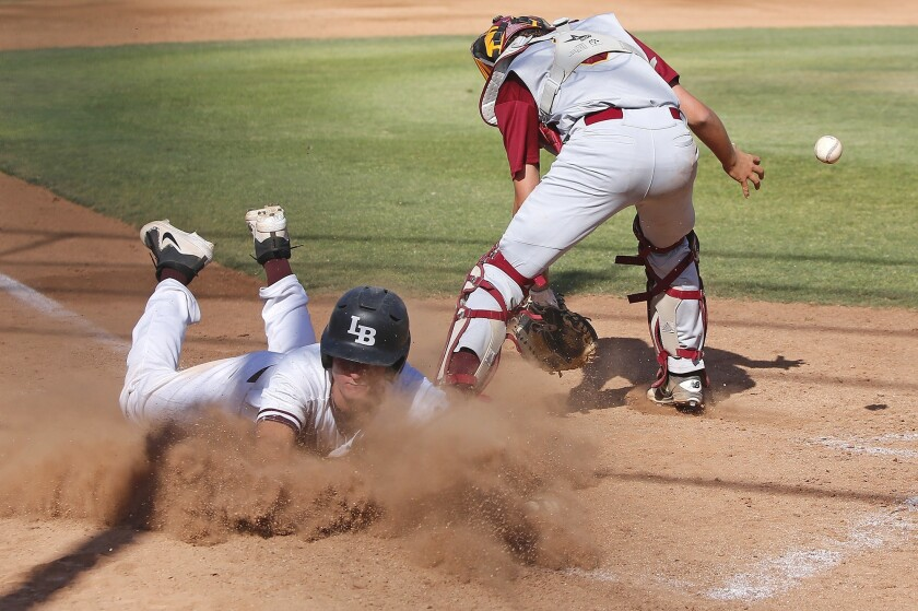 Laguna's Cutter Clawson dives across home plate safe as Estancia catcher tries to control the throw