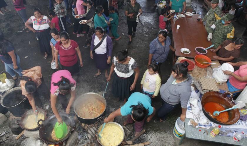 Varias mujeres preparan comida para personas en un albergue temporal en Papatlazolco, MÈxico, el lunes 8 de agosto de 2016. Las comunidades montaÒesas en dos estados mexicanos se recuperan de los aludes de lodo y tierra ocurridos el fin de semana que dejaron decenas de muertos durante fuertes lluvias a causa de los remanentes del hurac·n Earl. (AP Foto/Pablo Spencer)