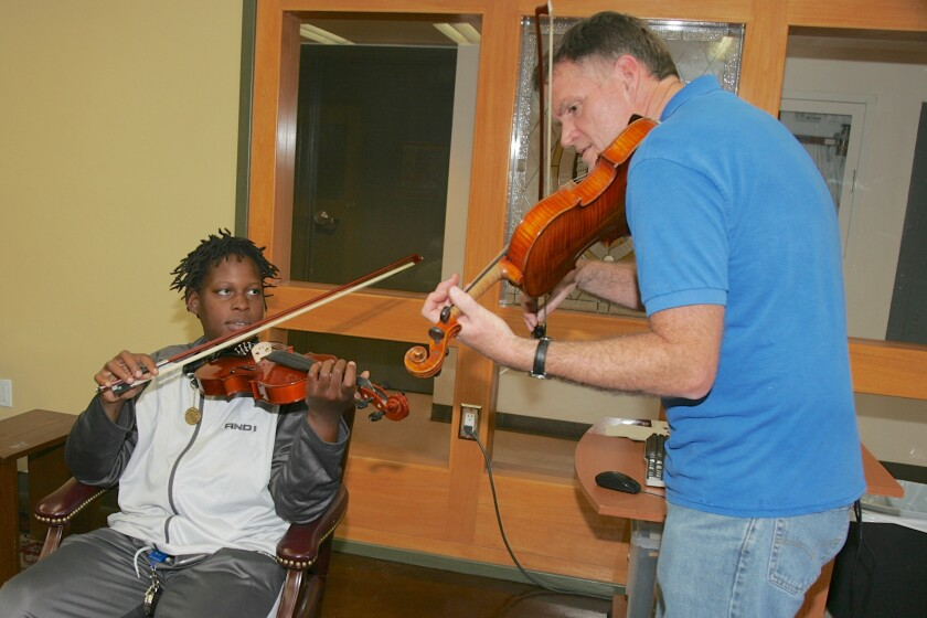 A music instructor for Doors of Change teaches a music lesson to a young San Diegan.