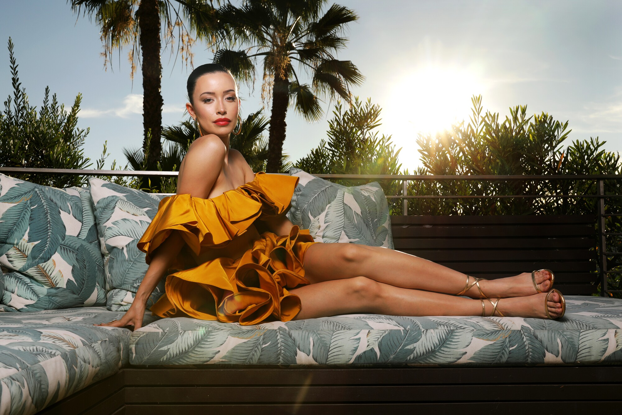 Actress Christian Serratos, in short ruffled dress and strappy shoes, strikes a pose on an outdoor deck.