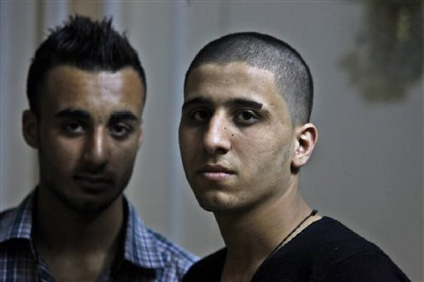 Ayman al-Sayed, 19, right, with his hair cut, and his friend Mohammed Hanouna, 18, left, pose for photo during an interview in Gaza City, Sunday, April 7, 2013. Al-Sayed used to have shoulder-length hair but says he was grabbed by Hamas police in a sweep along with other young men with long or gel-styled spiky hair last week, and that police shaved everyone's head. Hanouna still wears the hair-style that can now get young men in trouble in Gaza, during the Islamic militants latest attempt to imp