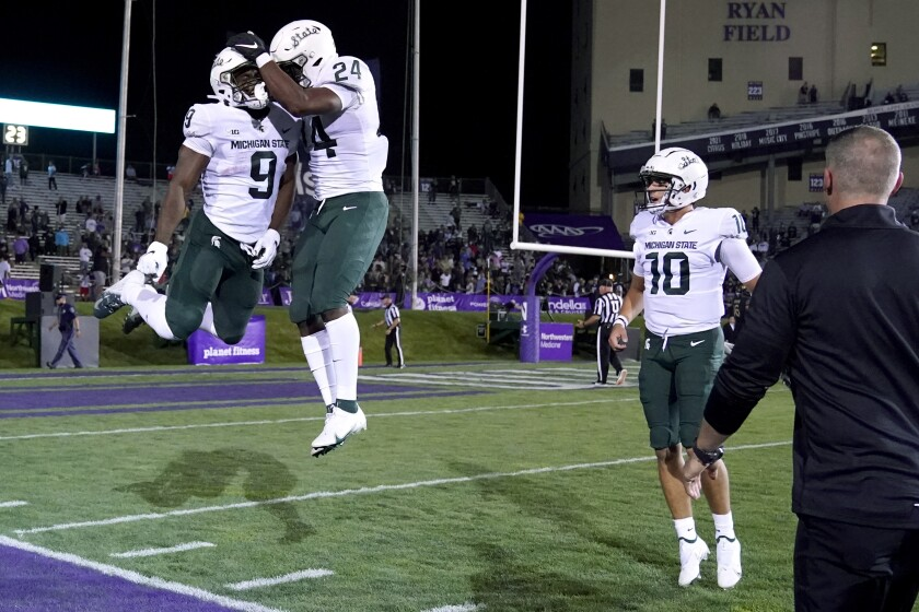 Michigan State running back Kenneth Walker III (9) celebrates with running back Elijah Collins (24) after Walker scored a touchdown during the first half against Northwestern in an NCAA college football game in Evanston, Ill., Friday, Sept. 3, 2021. At right is quarterback Payton Thorne. (AP Photo/Nam Y. Huh)