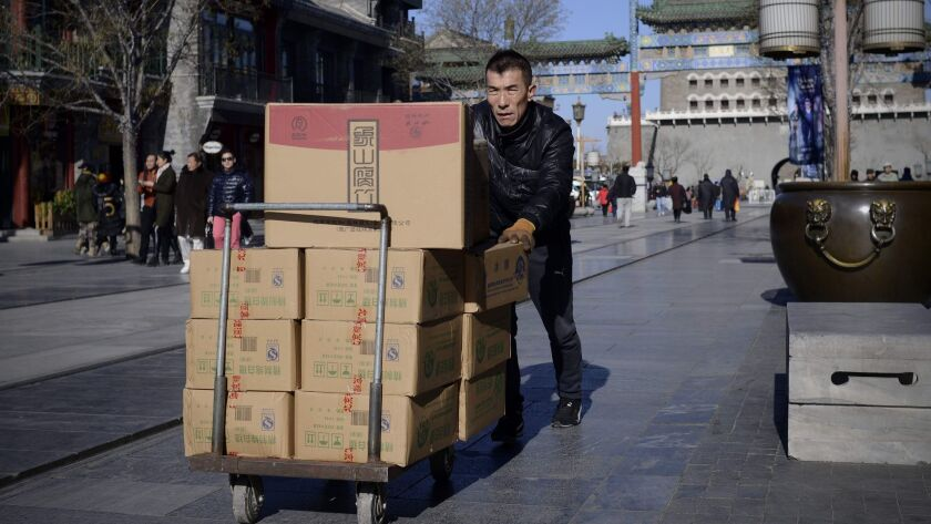A man pushes a trolley with goods along a street in Beijing in January 2017. China's producer prices rose at their swiftest pace in more than five years in December, according to the government.