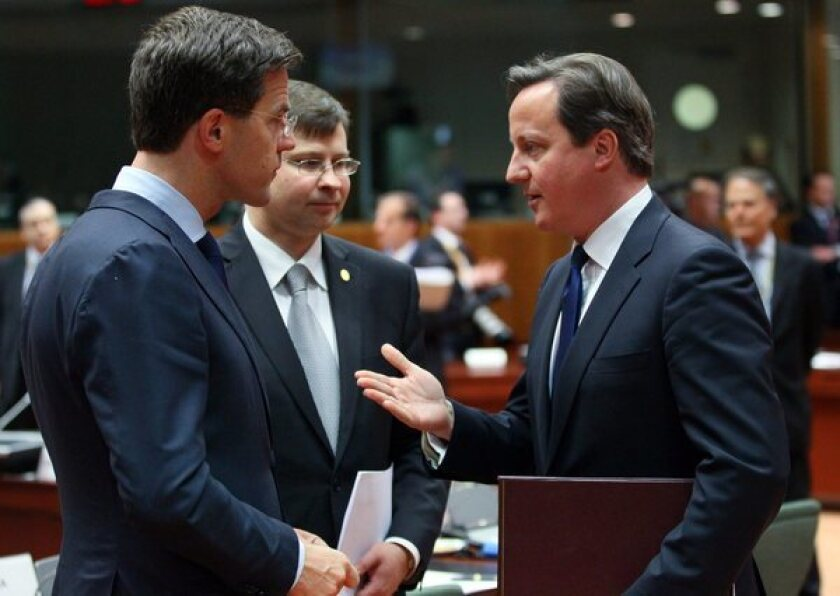 From left, Dutch Prime Minister Mark Rutte, Latvian Prime Minister Valdis Dombrovskis and British Prime Minister David Cameron chat during a European Council summit in Brussels.