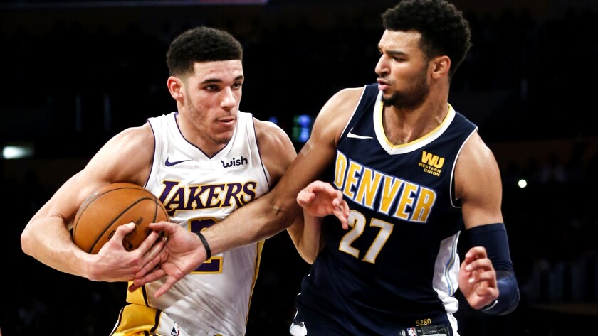 Lakers guard Lonzo Ball tries to drive past Nuggets guard Jamal Murray during the first half Sunday.