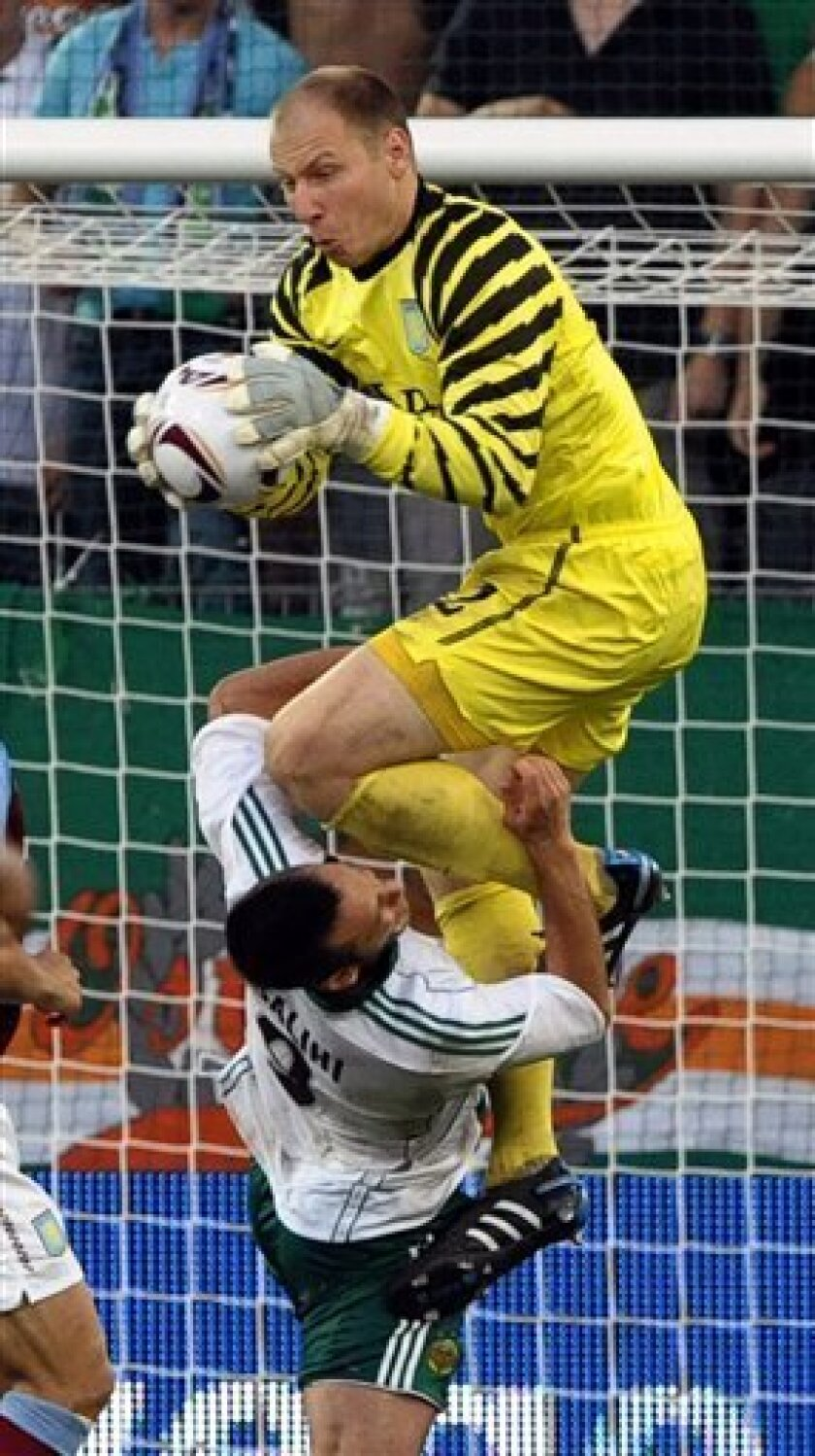 FILE - This is a Thursday, Aug. 19, 2010 file photo of Aston Villa's goalkeeper Brad Guzan as he grabs the ball from Rapid Vienna's Hamdi Salihi, during their Europa League play off round first leg soccer match in Vienna, Austria. American goalkeeper Brad Guzan has joined second-tier English side Hull on a one-month loan. The 26-year-old United States international is contracted to Premier League side Aston Villa but has been unable to oust fellow American Brad Friedel from the starting lineup. (AP Photo/dapd/Hans Punz, File)