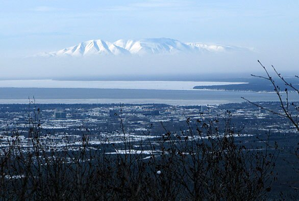 Ash from Mt. Redoubt volcano obscures the lower slopes of Mt. Susitna. The city of Anchorage is in the foreground. Ash coated communities in the Susitna Valley.