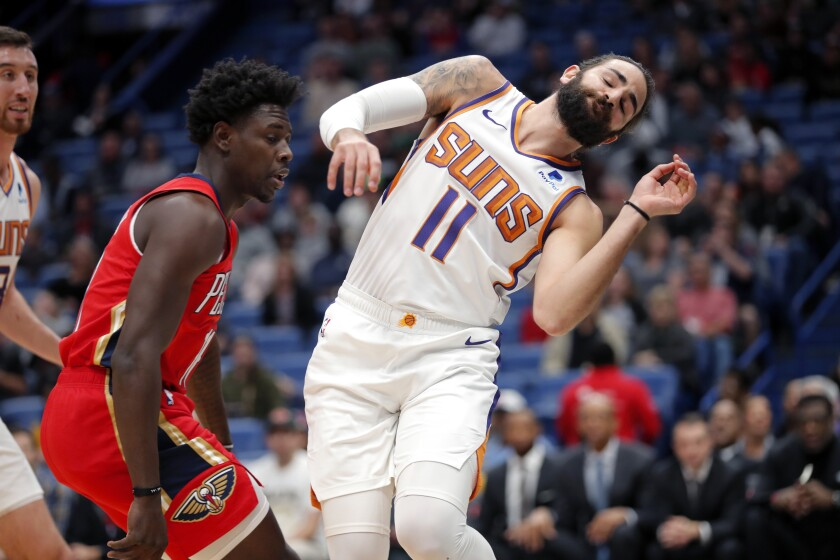 Phoenix Suns guard Ricky Rubio, right, collides with New Orleans Pelicans guard Jrue Holiday along the baseline while chasing the ball during the first half of an NBA basketball game in New Orleans, Thursday, Dec. 5, 2019. (AP Photo/Gerald Herbert)