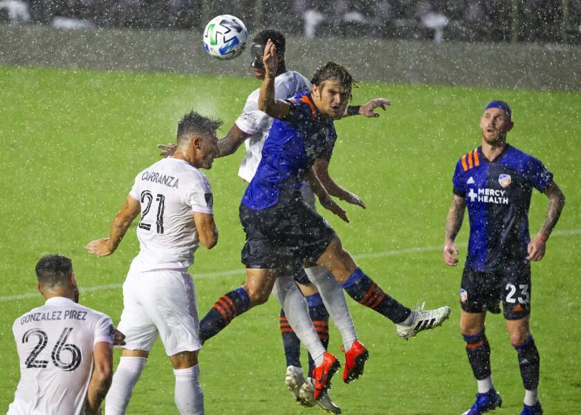 Inter Miami forward Julian Carranza (21) jumps for the ball with FC Cincinnati defender Nick Hagglund (14) during the second half of an MLS soccer match Sunday, Nov. 8, 2020, in Fort Lauderdale, Fla. (David Santiago/Miami Herald via AP)