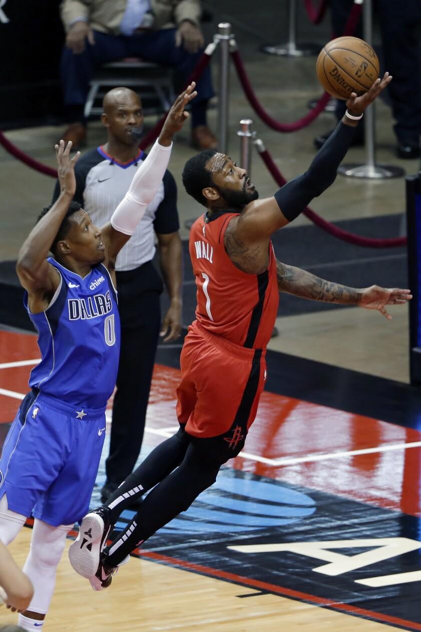 El base de los Rockets de Houston John Wall lanza el balón mientras lo defiende el base de los Mavericks de Dallas Josh Richardson en el encuentro del miércoles 7 de abril del 2021. (AP Photo/Michael Wyke, Pool)