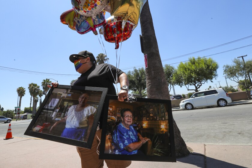Denise Vara brings balloons and photos of Lucy Reyes for her memorial service outside Mitla Cafe in San Bernardino.