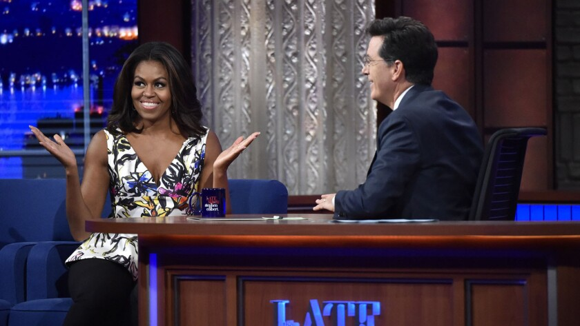 """First Lady Michelle Obama, left, appears with host Stephen Colbert during a taping of """"The Late Show with Stephen Colbert."""""""