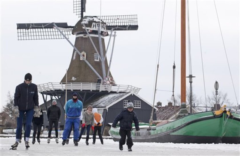 A boy, right, runs alongside skaters who pass a windmill in Woudsend, northern Netherlands, Wednesday Feb. 8, 2012. Dutch troops are joining a race against time to prepare ice for a legendary 125-mile (200 kilometer) race across frozen waterways in the northern Netherlands that could be staged for the first time in 15 years. Defense Ministry spokesman Peter Grotens says a group of 50 soldiers is shoveling snow along a possible alternative route in case ice on part of the traditional track of the Elfstedentocht, or 11 Cities Tour, is too weak to support the 16,000 skaters who would take part if organizers stage the race. (AP Photo/Peter Dejong)