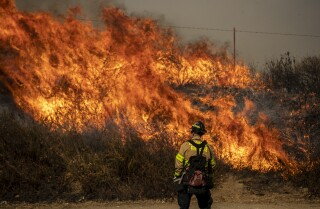 THOUSAND OAKS, CALIF. -- WEDNESDAY, OCTOBER 30, 2019: An Albuquerque firefighter watches as backfires burn in heavy brush along Madera Rd. as firefighters try to keep the Easy fire from crossing the road into Thousand Oaks, Calif., on Oct. 30, 2019. (Brian van der Brug / Los Angeles Times)