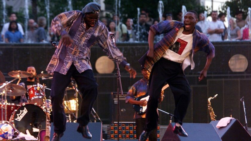 Oliver Mtukudzi, left, and a member of his band dance on stage during a 1999 performance at the California Plaza in Los Angeles.