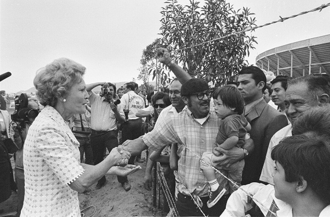 Former First Lady Pat Nixon shakes hands across the barbed wire border fence