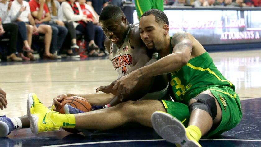 Arizona guard Rawle Alkins and Oregon forward Paul White battle for a loose ball in the first half.