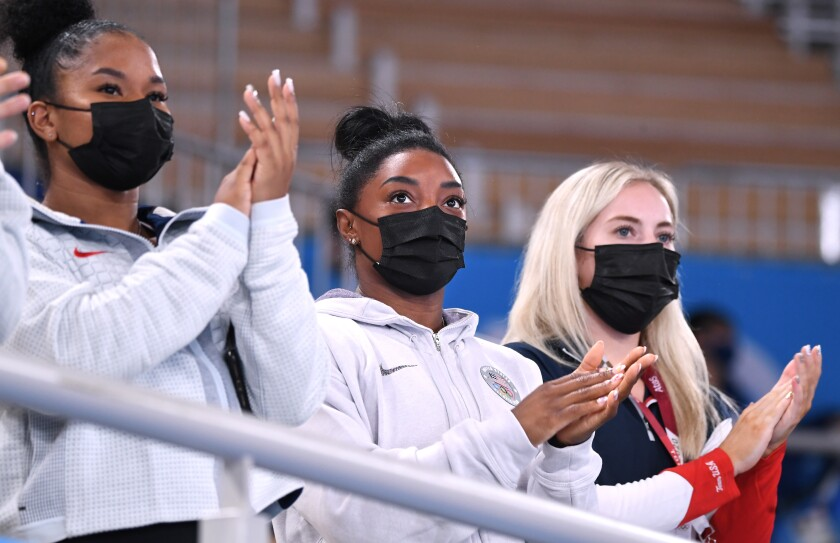 U.S. gymnast Simone Biles, center, applauds teammates from the stands.
