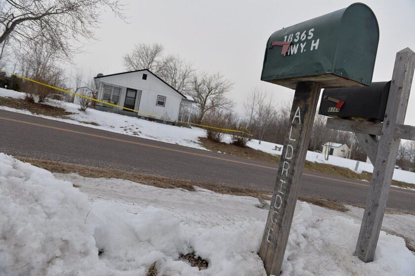 Police perimeter tape cordons off one of the crime scenes in Tyrone, Mo., where seven people were shot to death this week. The gunman then killed himself.