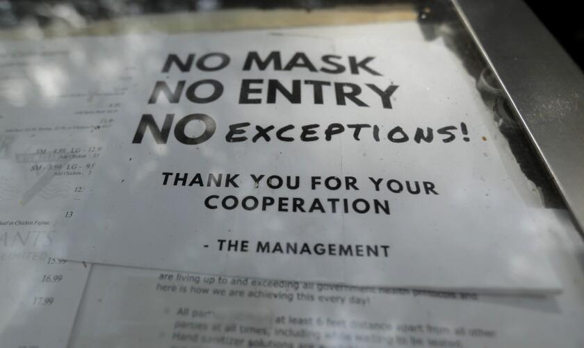 Un restaurante avisa en una puerta que no se permitirá la entrada a clientes que no lleven puesta mascarilla en Texas.